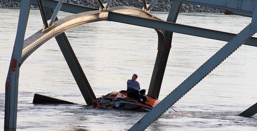 Description of . In this photo provided by Francisco Rodriguez, a man is seen sitting atop a car that fell into the Skagit River after the collapse of the Interstate 5 bridge there minutes earlier Thursday, May 23, 2013, in Mount Vernon, Wash. (AP Photo/Francisco Rodriguez)