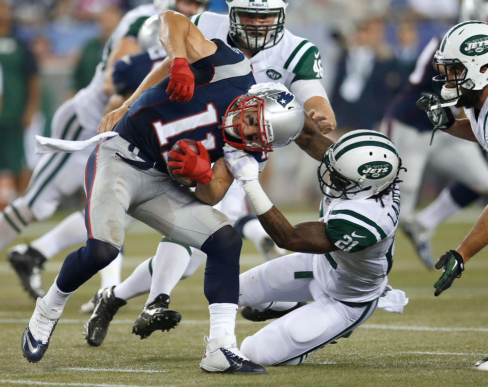 Description of . New York Jets defensive back Ellis Lankster (21) tries to tackle New England Patriots wide receiver Julian Edelman (11) during the second quarter of an NFL football game Thursday, Sept. 12, 2013, in Foxborough, Mass. (AP Photo/Elise Amendola)