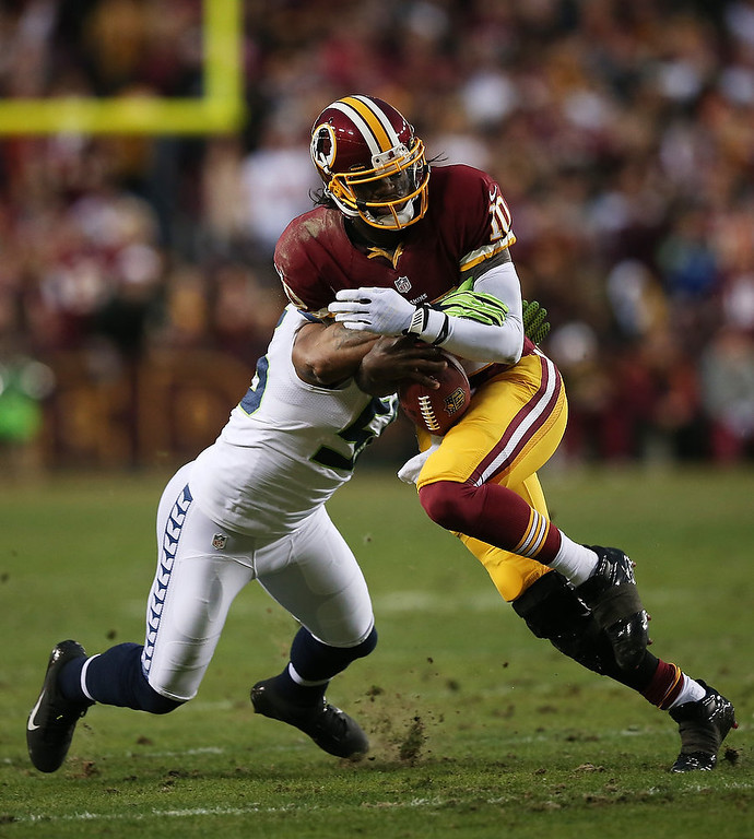Description of . Robert Griffin III #10 of the Washington Redskins is tackled by  Leroy Hill #56 of the Seattle Seahawks during the NFC Wild Card Playoff Game at FedExField on January 6, 2013 in Landover, Maryland.  (Photo by Win McNamee/Getty Images)
