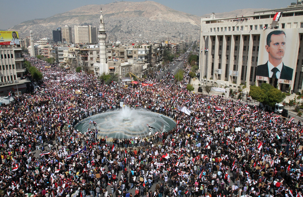 Description of . Thousands of Syrians rally to show their support for President Bashar al-Assad (portrait), who is facing unprecedented domestic pressure amid a wave of dissent, in Damascus on March 29, 2011. ANWAR AMRO/AFP/Getty Images