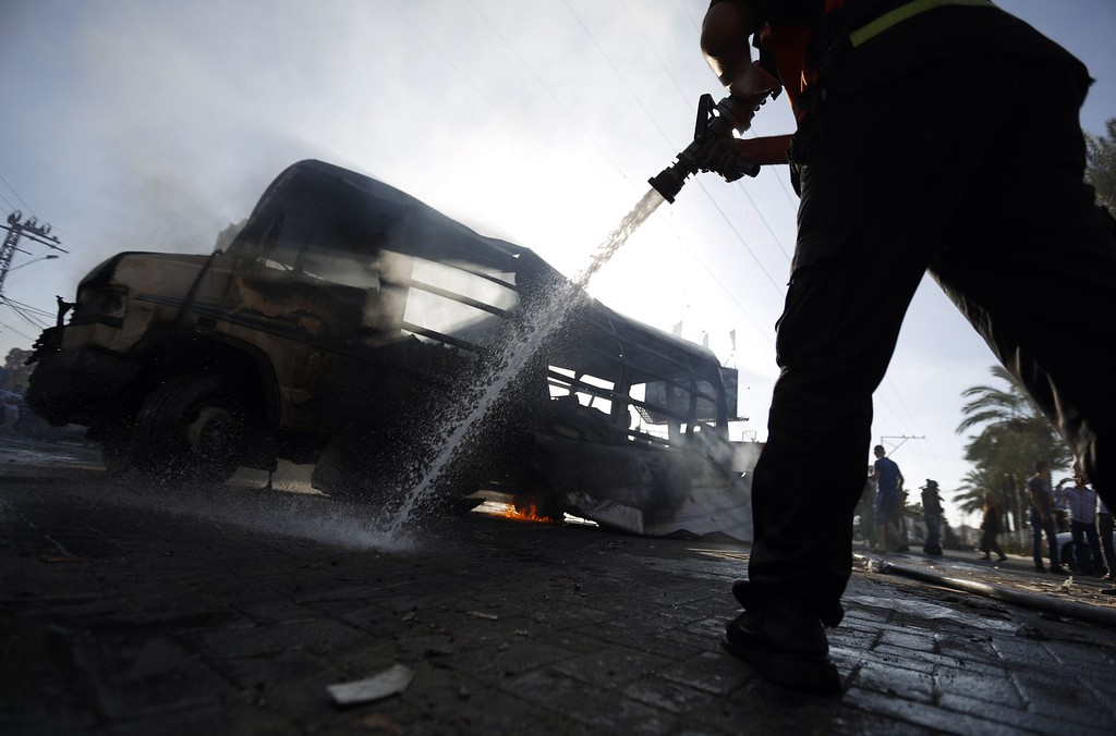 Description of . Palestinian firefighters try to extinguish the flames in a van, that was reportedly targeted by an Israeli military strike, in Gaza City on July 31, 2014. Israel said it would not pull troops from Gaza until they finish destroying a network of cross-border tunnels, despite sharp United Nations criticism over the Palestinian civilian death toll. AFP PHOTO/ MOHAMMED ABED/AFP/Getty Images