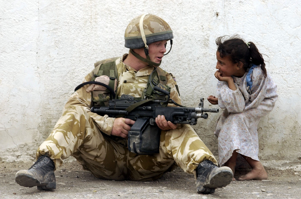 Description of . A British paratrooper, left, talks with an Iraqi girl while holding his position near the main street in Basra as coalition forces took control of much of Iraq\'s second city. (Hyoung Chang, The Denver Post)