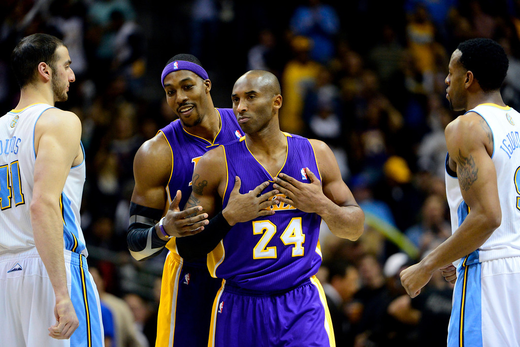 Description of . Los Angeles Lakers shooting guard Kobe Bryant (24) wipes his hands on his jersey as center Dwight Howard (12) leans over his shoulder against before the first half against the Denver Nuggets at the Pepsi Center on Wednesday, December 26, 2012. AAron Ontiveroz, The Denver Post