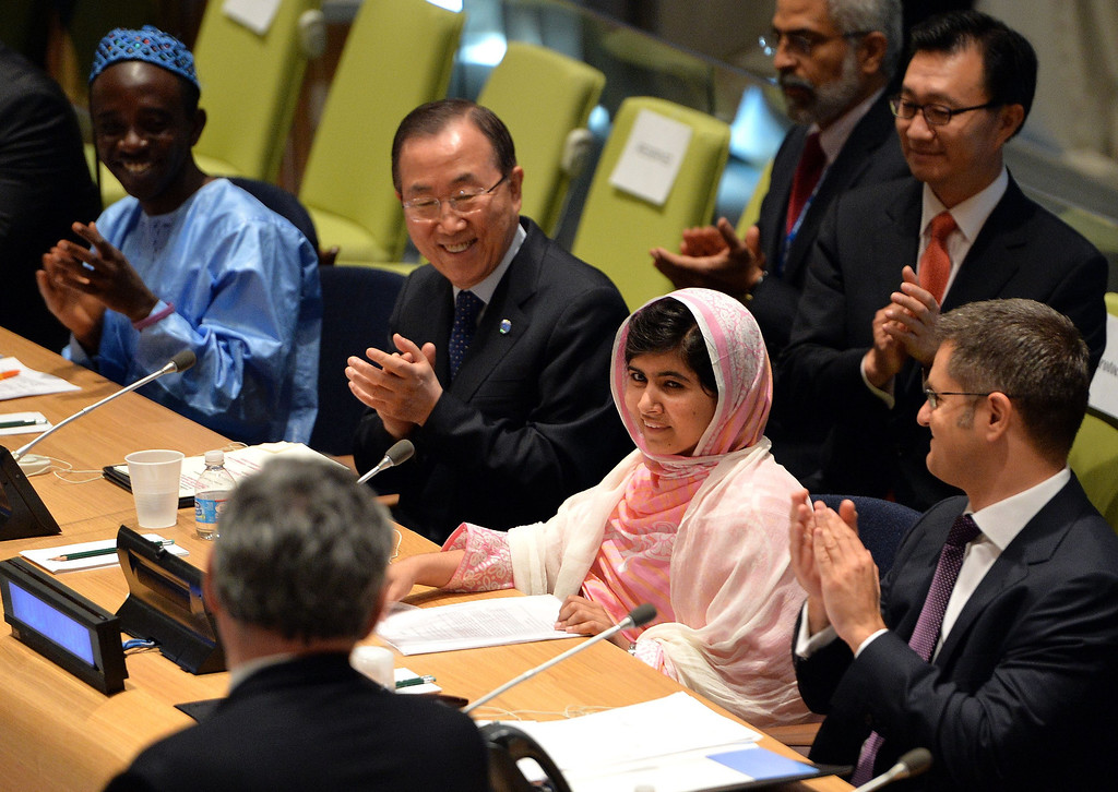 Description of . Pakistani student Malala Yousafzai is greeted by United Nations Secretary General Ban Ki-Moon (2nd L), Vuk Jeremic (R), President of the UN General Assembly, and Gordon Brown (L, back to camera), United Nations Special Envoy for Global  Education July 12, 2013 at UN headquarters in New York during the UN Youth Assembly. Yousafzai became a public figure when she was shot by the Taliban while travelling to school last year in Pakistan -- targeted because of her committed campaigning for the right of all girls to an education. The UN had declared July 12