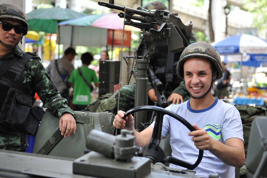 . A foreign tourist sits in a Thai Army vehicle as soldiers deploy on a downtown street after martial law was declared on May 20, 2014 in Bangkok, Thailand.  (Photo by Rufus Cox/Getty Images)