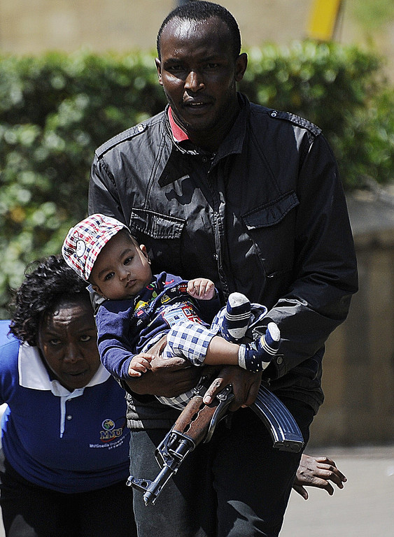 Description of . A policeman carries a baby to safety after masked gunmen stormed an upmarket mall and sprayed gunfire on shoppers and staff, killing at least six on September 21, 2013 in Nairobi. The Gunmen have taken at least seven hostages, police and security guards told an AFP reporter at the scene. AFP PHOTO/SIMON MAINA/AFP/Getty Images