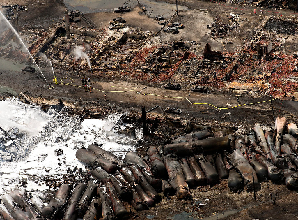 Description of . The downtown core lays in ruins as fire fighters continue to water smoldering rubble Sunday, July 7, 2013 in Lac Megantic, Quebec.    A runaway train derailed  Saturday igniting tanker cars carrying crude oil. (AP Photo/THE CANADIAN PRESS,Ryan Remiorz)