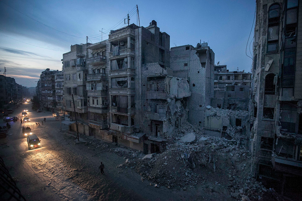 Description of . In this Thursday, Nov. 29, 2012 file photo, night falls on a Syrian rebel-controlled area as destroyed buildings, including Dar Al-Shifa hospital, are seen on Sa'ar street after airstrikes targeted the area last week, killing dozens in Aleppo, Syria. More than two years into Syria's civil war, the once highly-centralized authoritarian state has effectively split into three distinct parts, each boasting its own flags, security agencies and judicial system. (AP Photo/Narciso Contreras)