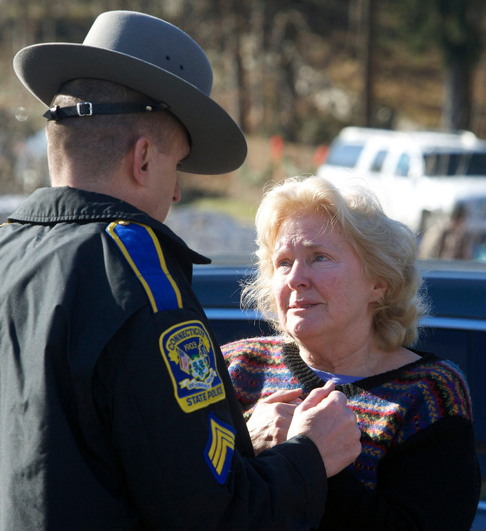 Description of . A woman speaks with a Connecticut State Trooper outside Sandy Hook Elementary School after a shooting in Newtown, Connecticut, December 14, 2012. A shooter opened fire at the elementary school in Newtown, Connecticut, on Friday, killing several people including children, the Hartford Courant newspaper reported.  REUTERS/Michelle McLoughlin