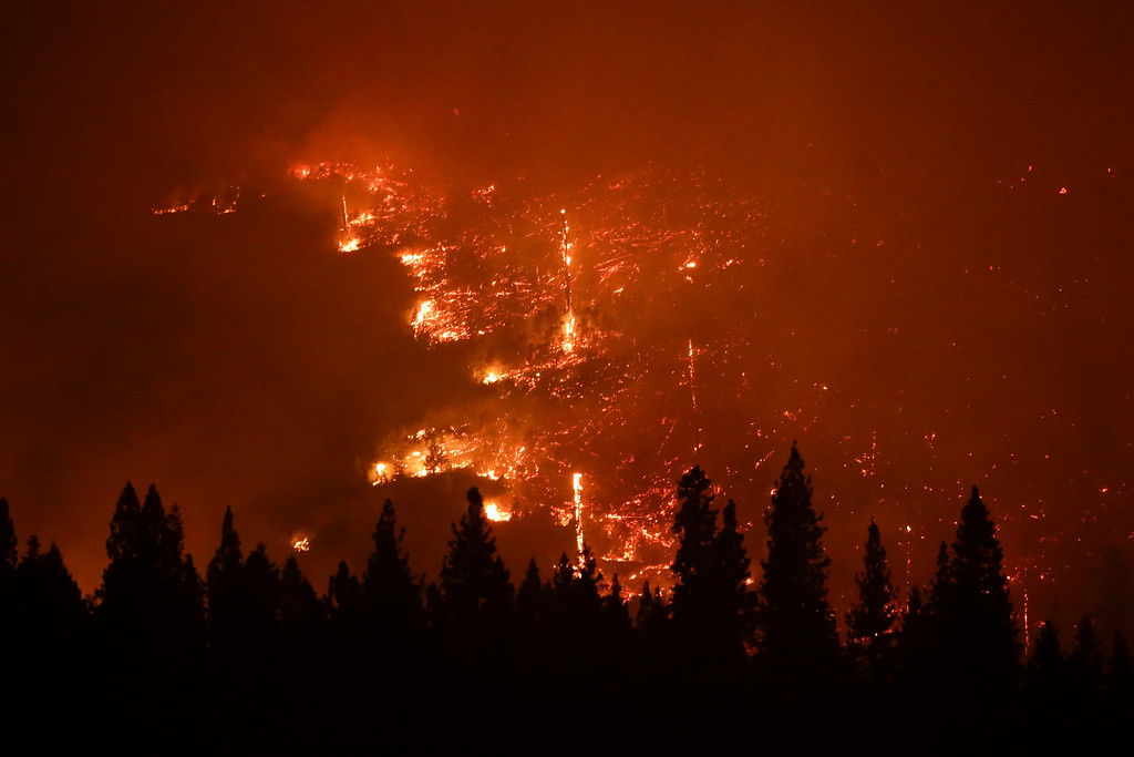 Description of . A forest smolders as the Rim Fire continues to burn near Yosemite National Park, Calif., on Saturday, Aug. 24, 2013.  (AP Photo/Jae C. Hong)