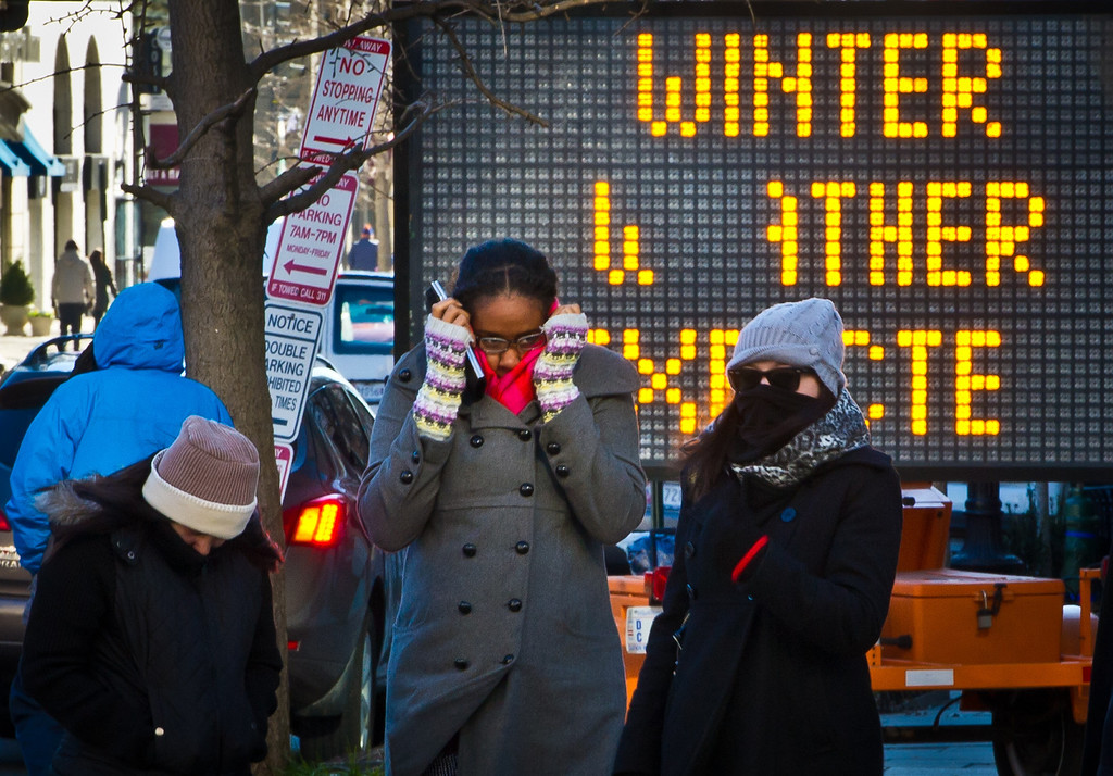 . Pedestrians bundled against the cold walk past a warning board as temperatures dipped into the single digits Fahrenheit and minus degrees with the wind chill on January 7, 2014 in Washington, DC. A blast of bone-chilling cold reaching lows not seen in two decades gripped the United States early Tuesday, snarling air travel, closing schools and prompting calls for people to stay inside. Superlatives of cold-talk abounded, even in midwestern states used to chest-high snow and bitter cold, as the National Weather Service said the deep freeze was making its way east. AFP PHOTO/MLADEN ANTONOV/AFP/Getty Images