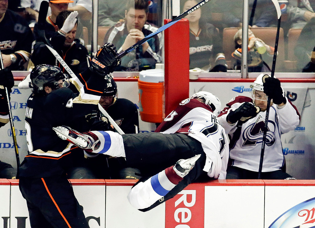 Description of . Anaheim Ducks right wing Bobby Ryan, left, knocks Colorado Avalanche right wing Milan Hejduk into the bench during the third period of an NHL hockey game in Anaheim, Calif., Sunday, Feb. 24, 2013. The Ducks won 4-3 in overtime. (AP Photo/Chris Carlson)