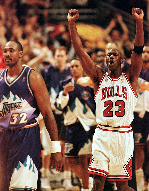 Description of . CHICAGO, IL - JUNE 14:  Michael Jordan (R) of the Chicago Bulls jumps in the air as Karl Malone (L) of the Utah Jazz walks off the court 13 June after game six of the 1997 NBA Finals at the United Center in Chicago, Illinois. Jordan was named the series MVP, leading the Bulls to a 4-2 series win over the Utah Jazz.  (PETER PAWINSKI/AFP/Getty Images)