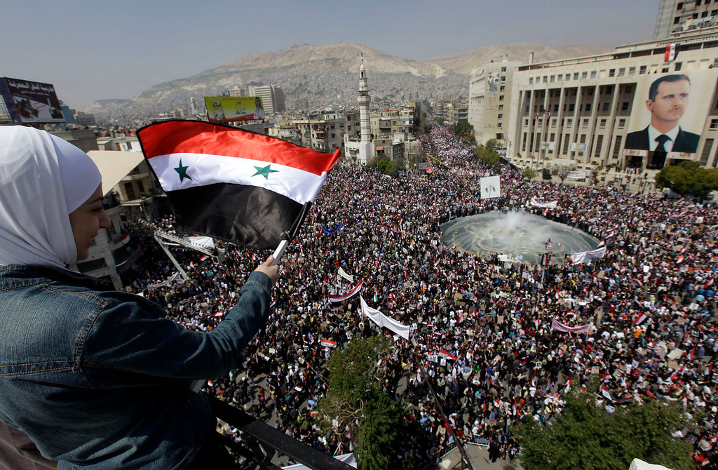 Description of . FILE - A supporter of Syrian President Bashar Assad waves a Syrian flag as she looks over a crowd gathered to show support for their president in Damascus, Syria, Tuesday, March 29, 2011. (AP Photo/Bassem Tellawi, File)