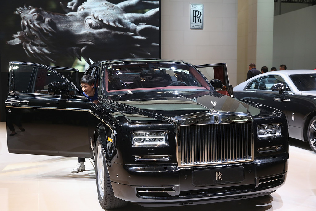 Description of . The potential consumer looks at a Rolls-Royce Phantom car during the 2014 Beijing International Automotive Exhibition at China International Exhibition Center on April 21, 2014 in Beijing, China. (Photo by Feng Li/Getty Images)