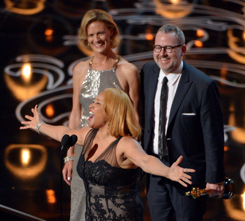 Description of . Darlene Love, center, sings as Janet Friesen, background left, and Morgan Neville accept the award for best documentary feature for ì20 Feet from Stardomî during the Oscars at the Dolby Theatre on Sunday, March 2, 2014, in Los Angeles.  (Photo by John Shearer/Invision/AP