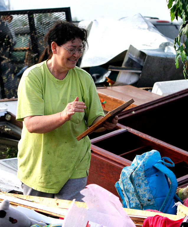 Description of . Teresa Ingram finds a picture of her daughter as she looks for belongings in the debris after a tornado passed through destroying Billy Barbs mobile home park on Tuesday, April 29, 2014, in Athens, Ala.  A dangerous storm system that spawned a chain of deadly tornadoes over three days flattened homes and businesses, forced frightened residents in more than half a dozen states to take cover and left tens of thousands in the dark Tuesday morning. (AP Photo/Butch Dill)