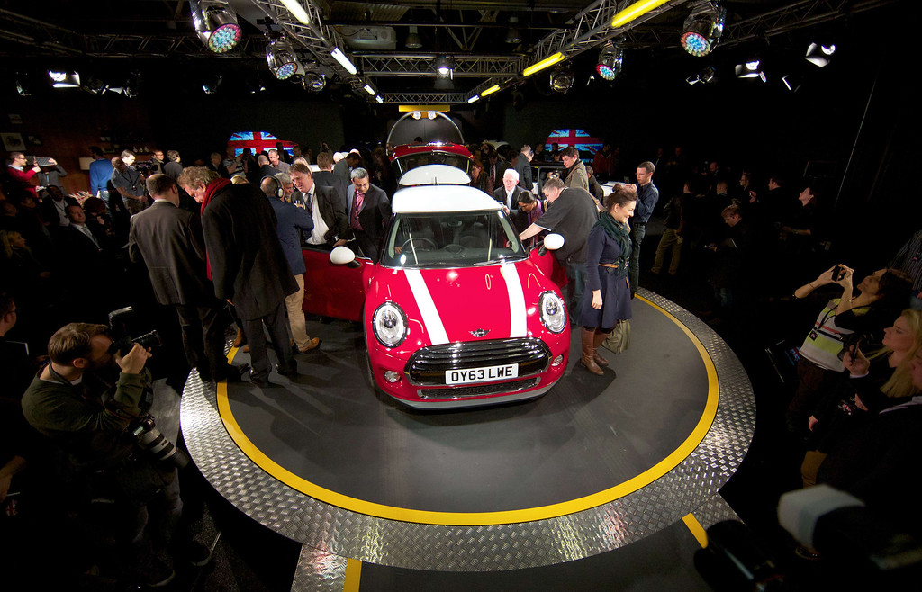 . Journalists inspect the new Mini Cooper during its official unveiling at BMW\'s plant at Cowley in Oxford, central England, on November 18, 2013. Car giant BMW, which has been manufacturing the Mini since 2001, has finally taken the wraps off the  new Mini that will be available in the UK in Spring 2014. ANDREW COWIE/AFP/Getty Images