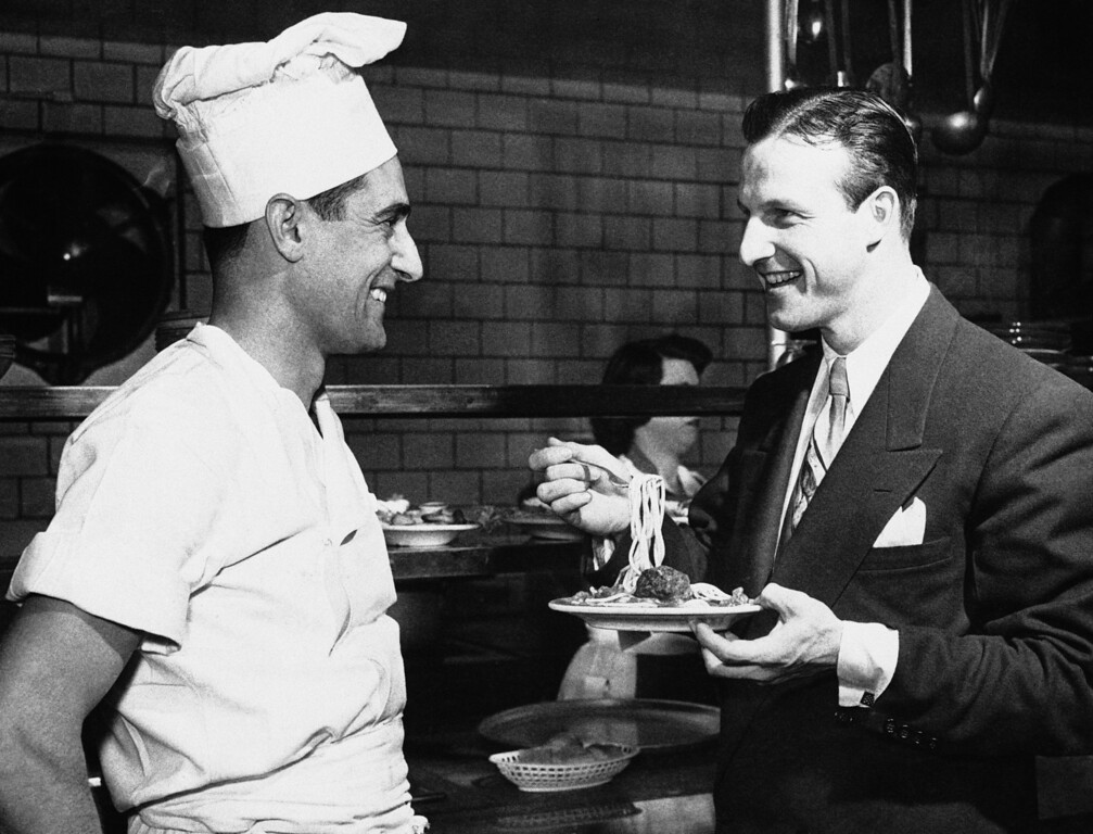 Description of . FILE- In this Feb. 18, 1951, file photo, Stan Musial eats spaghetti and talks to Chef Marie Ravetta in the kitchen of Stan Musial and Biggies restaurant in St. Louis, shortly after Musial signed his 1951 contract with the St. Louis Cardinals. Musial, one of baseball's greatest hitters and a Hall of Famer with the Cardinals for more than two decades, has died. He was 92. Stan the Man won seven National League batting titles, was a three-time MVP and helped the Cardinals capture three World Series championships in the 1940s. The Cardinals announced Musial's death in a news release. They said he died Saturday evening, Jan. 19, 2013, at his home surrounded by family. (AP Photo/File)