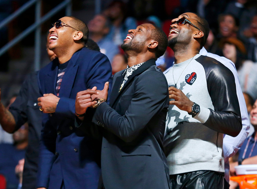 Description of . NBA players Carmelo Anthony, Dwyane Wade and LeBron James (L-R) watch the slam dunk contest during the NBA basketball All-Star weekend in Houston, Texas, February 16, 2013. REUTERS/Jeff Haynes