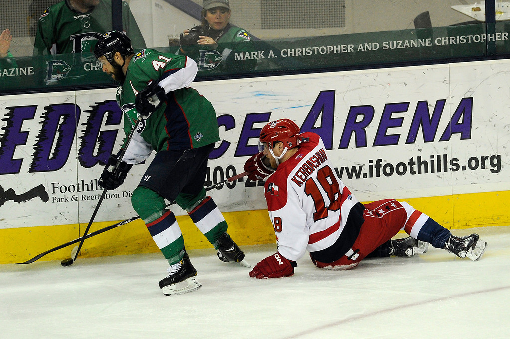 Description of . DENVER, CO - MAY 2: Kale Kerbashian (18) of the Allen Americans attempts to poke check the puck away from Garett Bembridge (41) of the Denver Cutthroats during the second period of game 1 of the Ray Miron Presidents Cup Finals at the Denver Coliseum in Denver, Colorado on May 2, 2014. (Photo by Seth McConnell/The Denver Post)