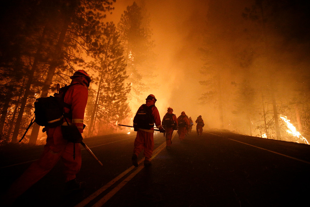Description of . Inmate firefighters walk along state Highway 120 as firefighters continue to battle the Rim Fire near Yosemite National Park, Calif., on Sunday, Aug. 25, 2013.  (AP Photo/Jae C. Hong)