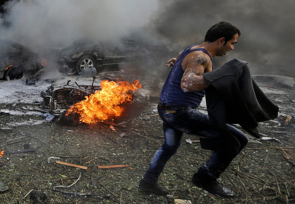 Description of . A Lebanese man runs in front of a burned car, at the scene where two explosions have struck near the Iranian Embassy killing many, in Beirut, Lebanon, Tuesday Nov. 19, 2013.  (AP Photo/Hussein Malla)