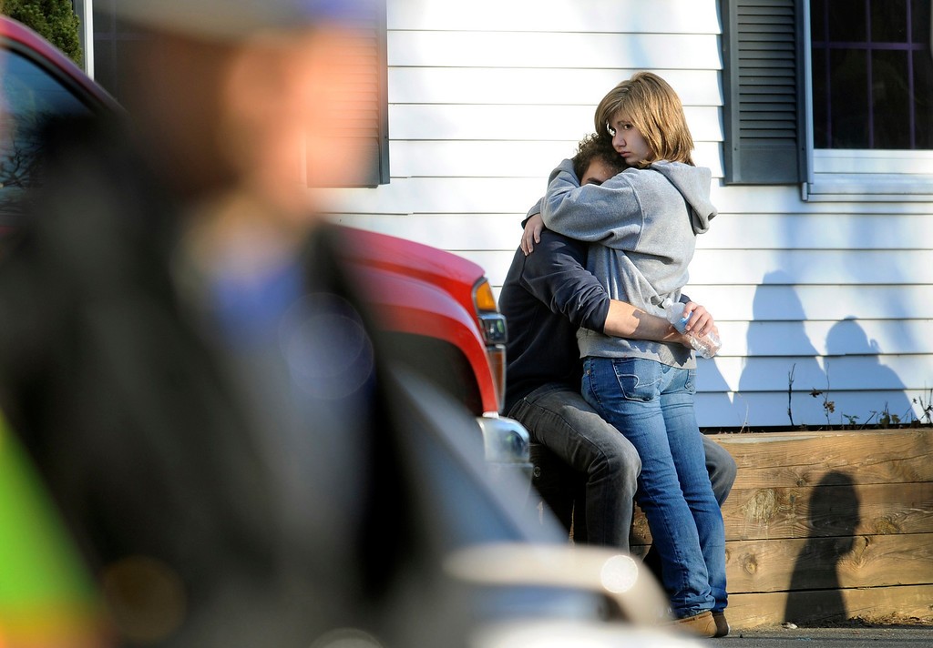 Description of . People embrace at a firehouse staging area for family around near the scene of a shooting at the Sandy Hook Elementary School in Newtown, Conn. where authorities say a gunman opened fire, leaving 27 people dead, including 20 children, Friday, Dec. 14, 2012. (AP Photo/Jessica Hill)