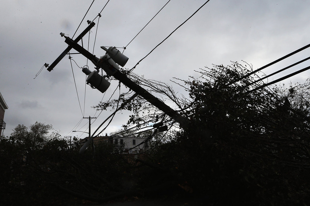 ". Power lines rest at a 45 degree angle on Clinton Avenue in the aftermath of Hurricane Sandy on October 30, 2012 in Huntington, New York. The storm has claimed at least a few dozen lives in the United States, and has caused massive flooding across much of the Atlantic seaboard. U.S. President Barack Obama has declared the situation a ""major disaster\"" for large areas of the U.S. east coast, including New York City.  (Photo by Bruce Bennett/Getty Images)"