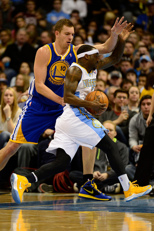 Description of . Denver Nuggets point guard Ty Lawson (3) drives past Golden State Warriors power forward David Lee (10) during the second half of the Nuggets' 116-105 win at the Pepsi Center on Sunday, January 13, 2013. AAron Ontiveroz, The Denver Post