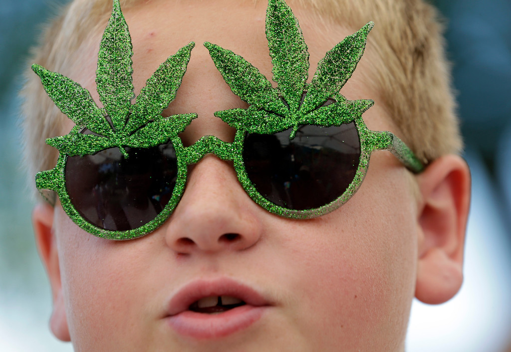 . Tommy Gibbons, 14, sports marijuana-themed sunglasses at the first day of Hempfest, Friday, Aug. 16, 2013, in Seattle. Thousands packed the Seattle waterfront park for the opening of a three-day marijuana festival � an event that is part party, part protest and part victory celebration after the legalization of pot in Washington and Colorado last fall. Hempfest was expected to draw as many as 85,000 people per day. (AP Photo/Elaine Thompson)
