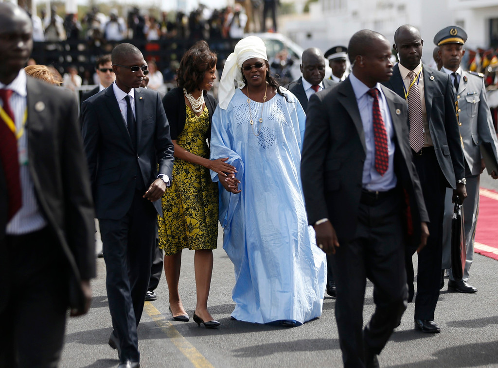 Description of . U.S. first lady Michelle Obama walks with Marieme Faye, wife of Senegal's President Macky Sall, to Air Force One as the first lady and U.S. President Barack Obama depart Dakar June 28, 2013. REUTERS/Jason Reed