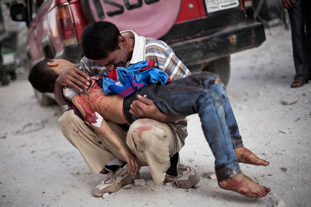 Description of . Syrian man cries while holding the body of his son near Dar El Shifa hospital in Aleppo, Syria, Wednesday, Oct. 3, 2012. (AP Photo/ Manu Brabo)