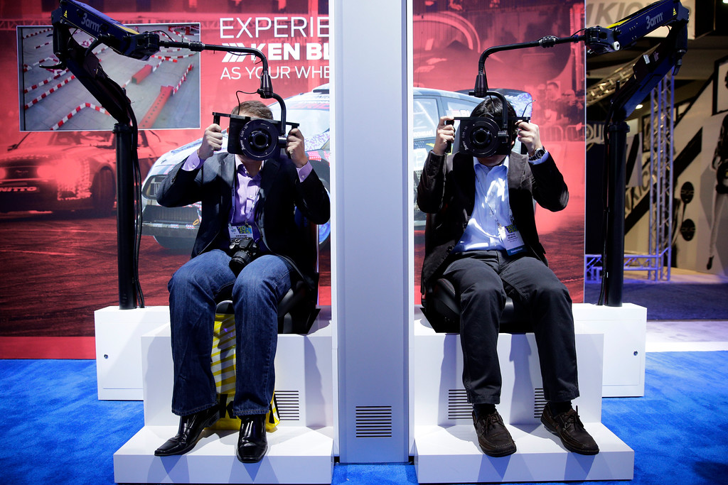 Description of . Show attendees try driving simulators at the Ford booth at the International Consumer Electronics Show(CES) on Wednesday, Jan. 8, 2014, in Las Vegas. (AP Photo/Jae C. Hong)