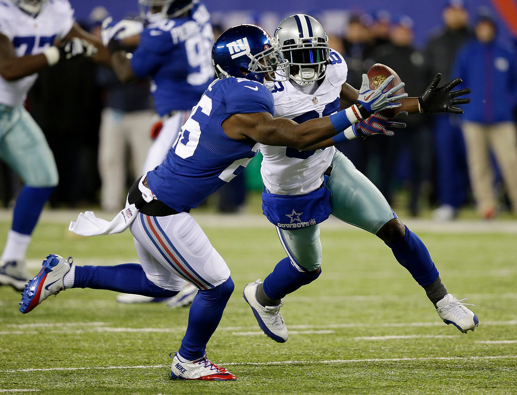 Description of . New York Giants strong safety Antrel Rolle, left, intercepts a pass intended for Dallas Cowboys wide receiver Dez Bryant, right, during the first half of an NFL football game Sunday, Nov. 24, 2013, in East Rutherford, N.J. (AP Photo/Seth Wenig)