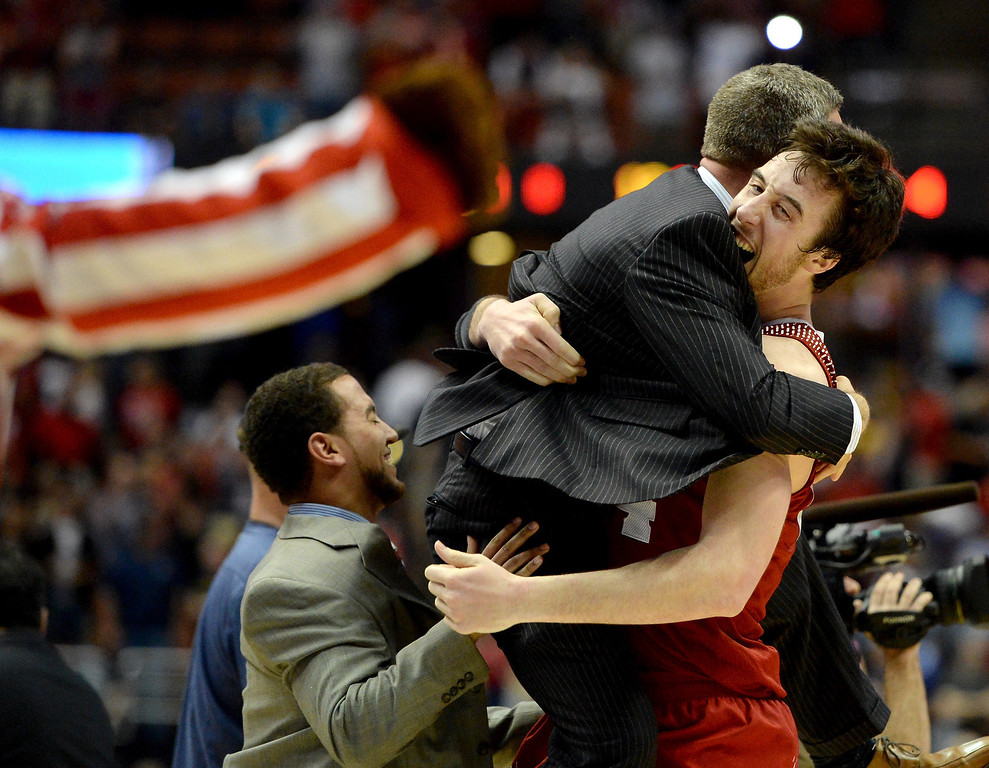 Description of . Frank Kaminsky #44 of the Wisconsin Badgers celebrates with teammates after defeating the Arizona Wildcats 64-63 in overtime during the West Regional Final of the 2014 NCAA Men's Basketball Tournament at the Honda Center on March 29, 2014 in Anaheim, California.  (Photo by Harry How/Getty Images)
