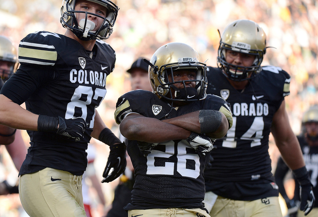 Description of . University of Colorado's Tony Jones (26) celebrates a touchdown in the third quarter of the game against Utah at Folsom Field on November 23, 2012.   Hyoung Chang, The Denver Post