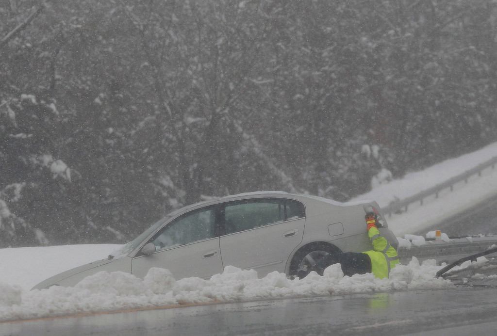 Description of . A tow truck operator attempts to remove a car that crashed during a massive blizzard in the median of Highway 50 near Winchester, Virginia, outside of Washington, March 6, 2013. REUTERS/Gary Cameron