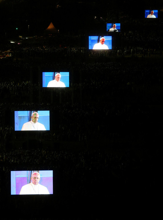 Description of . Pope Francis is projected on screens at Copacabana beach in Rio de Janeiro, July 25, 2013. Pope Francis is on the fourth day of his week-long visit for World Youth Day.  REUTERS/Paulo Whitaker