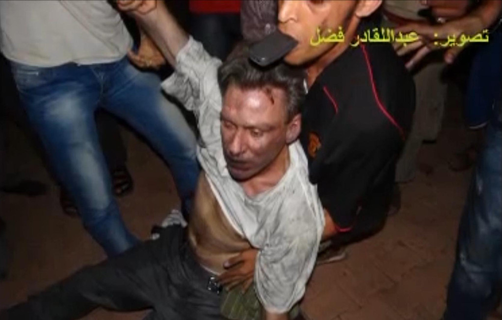 Description of . In this Sept. 11, 2012 file photo, this still image included in a video obtained by the Associated Press from Fahd al-Bakoush, a freelance videographer and activist, which has been authenticated based on its contents and other AP reporting, shows the body of U.S. Ambassador Chris Stevens being moved by Libyan civilians trying to rescue him after gunmen and protesters rampaged through the U.S. consulate in Benghazi, Libya. The group of Libyans had stumbled across Stevens' seemingly lifeless form inside a dark room and didn't know who he was, only that he was a foreigner, al-Bakoush and two other witnesses told the AP. The Arabic script in the photo translates into English as,