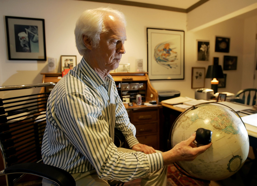 Description of . Former astronaut Rusty Schweickart holds a 3-D model of the asteroid 1998 KY26 near the spot on the globe where an asteroid could hit the earth, during a photo session at his home in Tiburon, Calif., Nov. 1, 2005. Schweickart is currently the chairman of the B612 Foundation. (AP Photo/Eric Risberg)