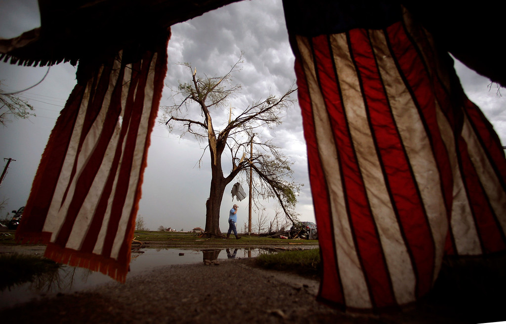 Description of . Monty Montgomery walks among rubble as he prepares to clean up a friend's tornado-ravaged home Thursday, May 23, 2013, in Moore, Okla. Cleanup continues three days after a huge tornado roared through the Oklahoma City suburb, flattening a wide swath of homes and businesses. (AP Photo/Charlie Riedel)