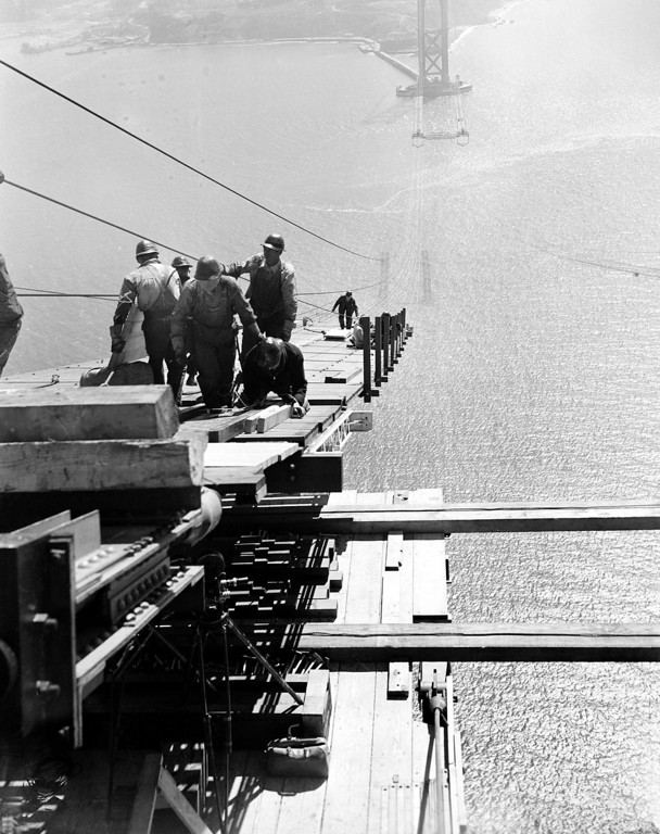 Description of . Workmen wearing steel helmets lay the catwalks for the Golden Gate Bridge in San Francisco, Ca., Sept. 19, 1935.  Spinning of the big suspension cables will start after the two catwalks are laid high above the Golden Gate Strait.  (AP Photo)