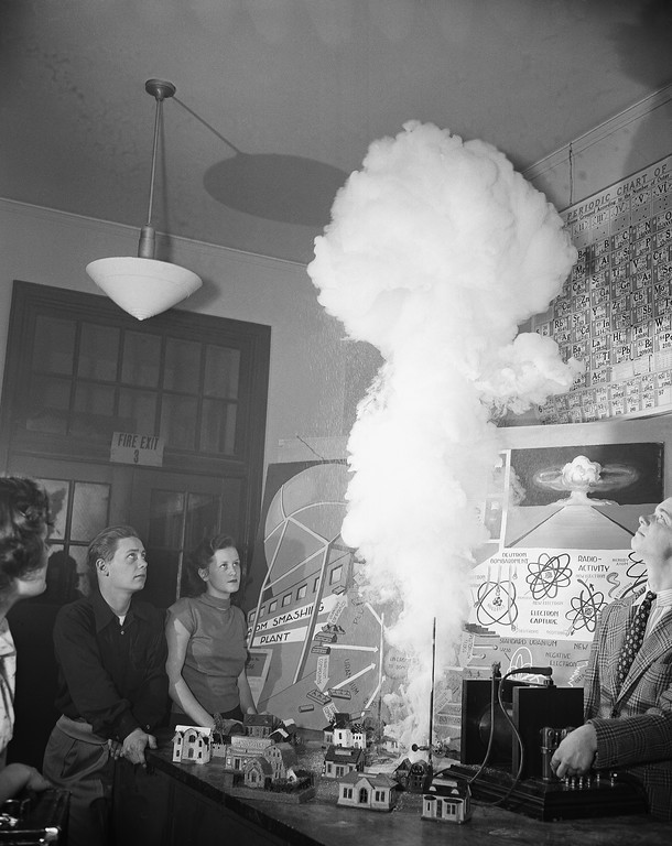 Description of . Students set off a simulated atomic bomb explosion during classroom study of atomic energy at Anacostia High School in Washington D.C., March 25, 1950. The explosion was made by igniting a mixture of Sulfur and Zinc with a high frequency spark and the model houses are used to compare the size of the smoke cloud. The students are, left to right: Charles Jones, Joan Collinge and Charles Williams. (AP Photo/Henry Burroughs)