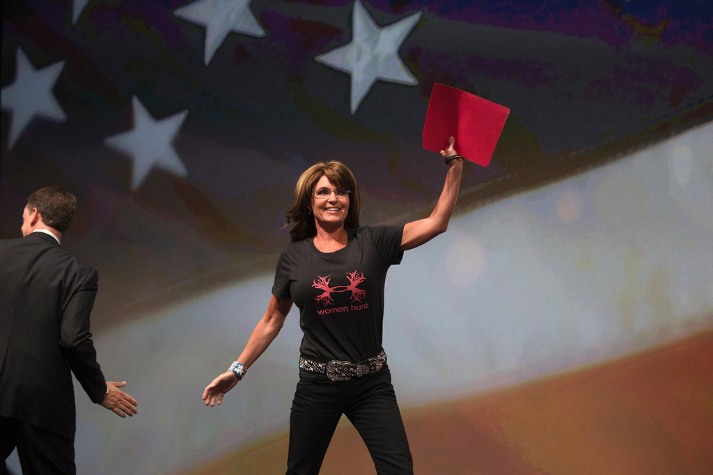 Description of . Former Alaska Governor Sarah Palin waves as she enters the stage to speak during the NRA-ILA Leadership Forum at the George R. Brown Convention Center, the site for the National Rifle Association's annual meeting in Houston, Texas on May 3, 2013. President Barack Obama and national media are demonizing law-abiding gun owners in the wake of recent violent acts, National Rifle Association leaders and political allies said on Friday at its first convention since the Connecticut school massacre. Organizers expect some 70,000 attendees at the 142nd NRA Annual Meetings & Exhibits in Houston, which began on Friday and continues through Sunday.  REUTERS/Adrees Latif