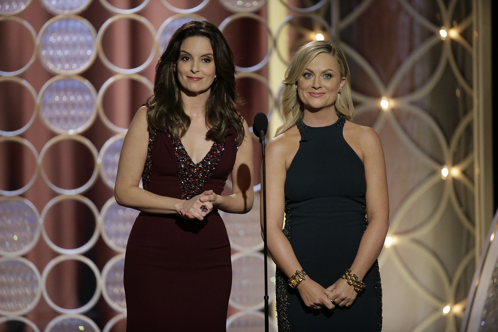 Description of . In this handout photo provided by NBCUniversal,  Hosts Tina Fey and Amy Poehler speak onstage during the 71st Annual Golden Globe Award at The Beverly Hilton Hotel on January 12, 2014 in Beverly Hills, California.  (Photo by Handout/Getty Images)