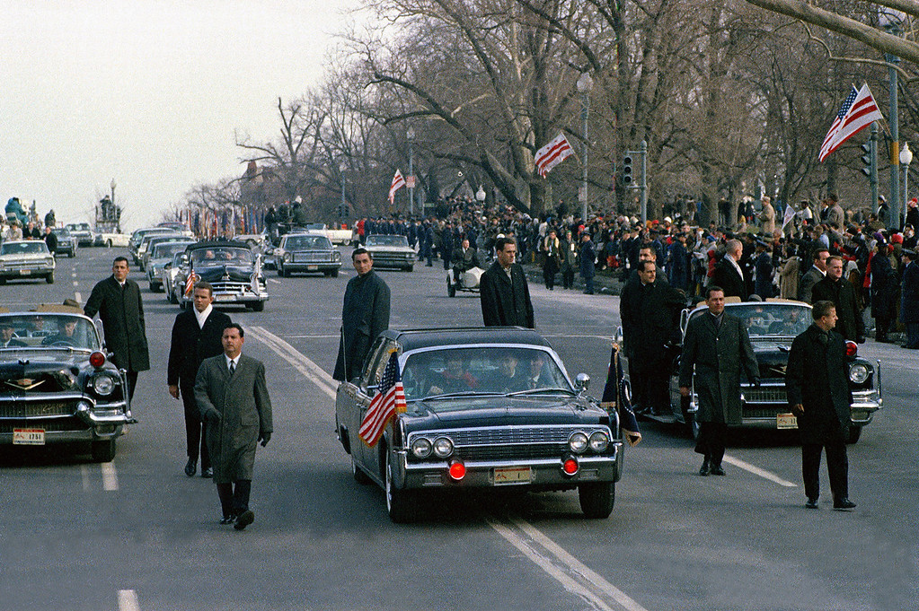 Description of . The motorcade carrying President-elect Lyndon B. Johnson and his wife Lady Bird Johnson is shown en route to the Capitol building as secret service agents run alongside of the closed car in Washington, D.C., Jan. 20, 1965. Johnson would be sworn in as the 36th president of the United States. (AP Photo)