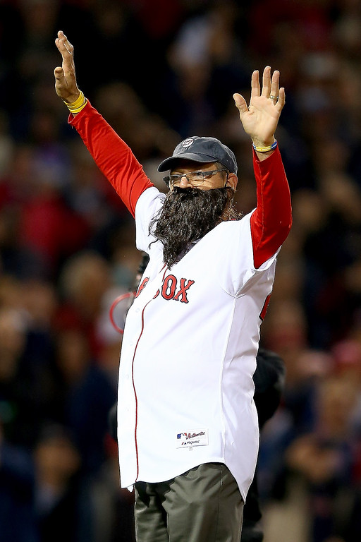 Description of . Former Boston Red Sox player Carlton Fisk reacts before throwing out the ceremonial first pitch prior to Game Six of the 2013 World Series between the Boston Red Sox and the St. Louis Cardinals at Fenway Park on October 30, 2013 in Boston, Massachusetts.  (Photo by Elsa/Getty Images)