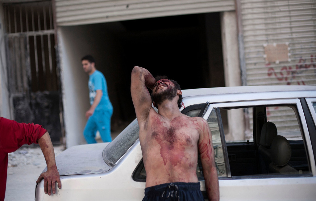 Description of . FILE - A Syrian man cries outside the Dar El Shifa hospital in Aleppo, Syria, after his daughter was injured during a Syrian Air Force strike over a school where hundreds of refugees had taken shelter Thursday, Oct. 4, 2012. (AP Photo/Manu Brabo, File)