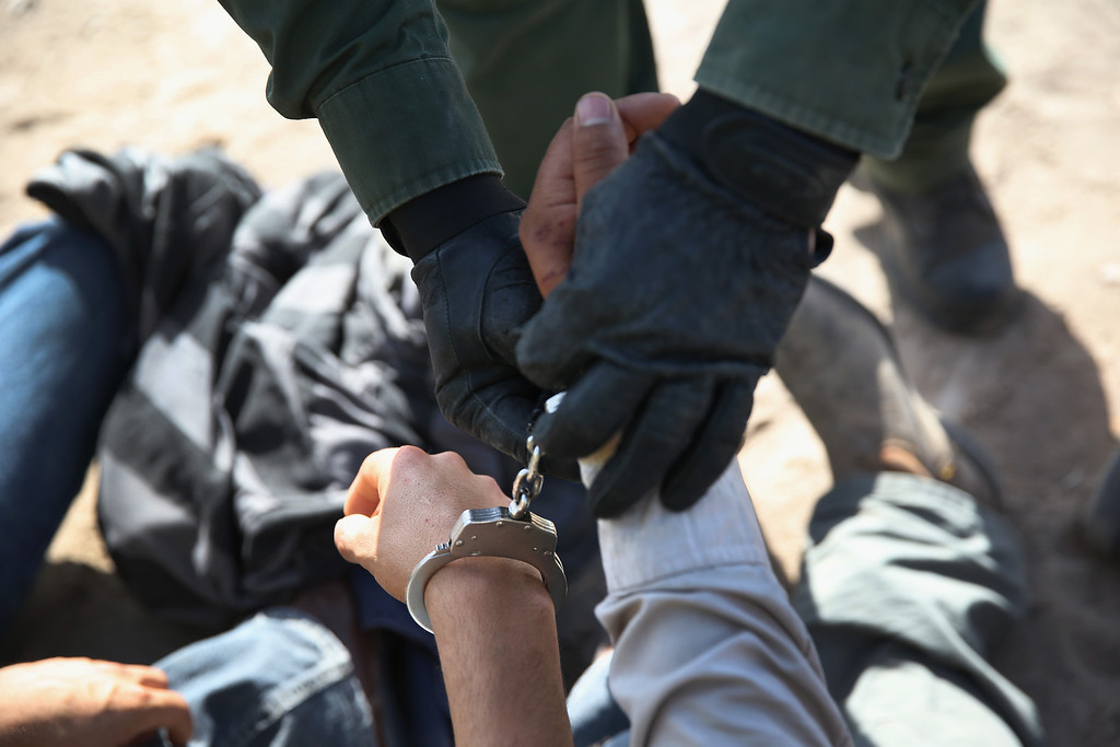 Description of . MISSION, TX - APRIL 11:  A U.S. Border Patrol agent handcuffs an undocumented immigrant near the U.S.-Mexico border on April 11, 2013 near Mission, Texas. A group of 16 immigrants from Mexico and El Salvador said they crossed the Rio Grande River from Mexico into Texas during the morning hours before they were caught. The Rio Grande Valley sector of has seen more than a 50 percent increase in illegal immigrant crossings from last year, according to the Border Patrol. Agents say they have also seen an additional surge in immigrant traffic since immigration reform negotiations began this year in Washington D.C. Proposed refoms could provide a path to citizenship for many of the estimated 11 million undocumented workers living in the United States. Photo by John Moore/Getty Images)  (Photo by John Moore/Getty Images)